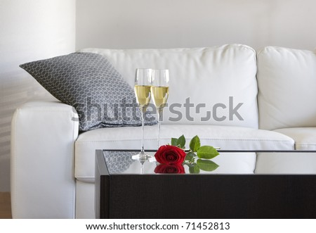 champagne and red rose on table in modern living room - stock photo