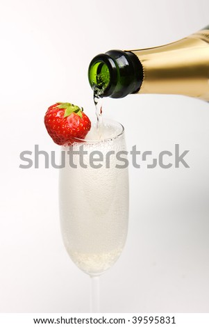 Champagne been poured in a flute with strawberry