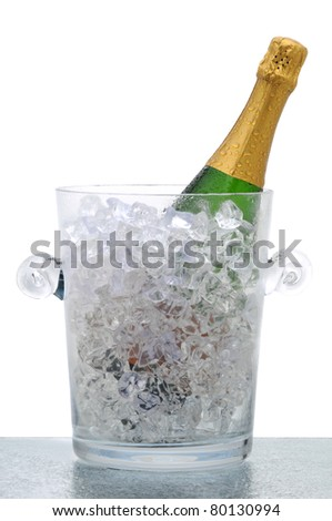 Champagne bottle in a crystal bucket filled with ice. Vertical format isolated on white, - stock photo