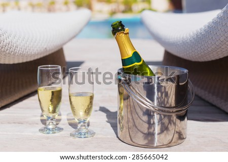 Champagne bottle in bucket and two glasses of champagne - stock photo