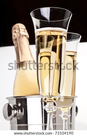 Champagne bottle in cooler and two champagne glasses. - stock photo