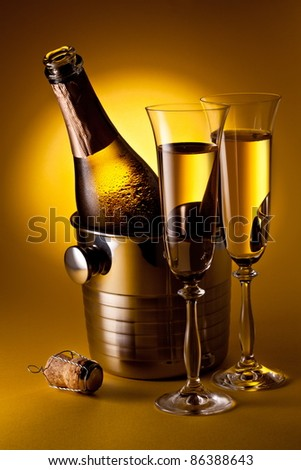 Champagne bottle in cooler and two champagne glasses. On a yellow background. - stock photo