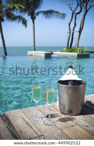 Champagne bottle in ice bucket and champagne glasses by swimming pool - stock photo