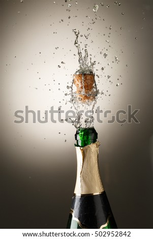 Champagne bottle with cork popping and splash
