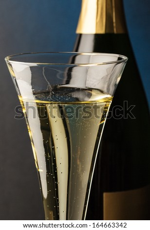 champagne bottle with glass of champagne. symbolic photo for celebrations and new year. - stock photo