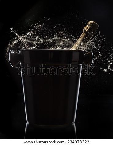 Champagne bucket on black background, celebration theme. - stock photo