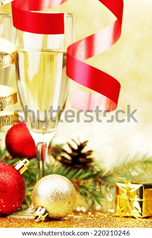 Champagne, fir tree, christmas decor and gifts on golden background