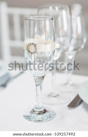 Champagne flute decorated with silk ribbon and brooch