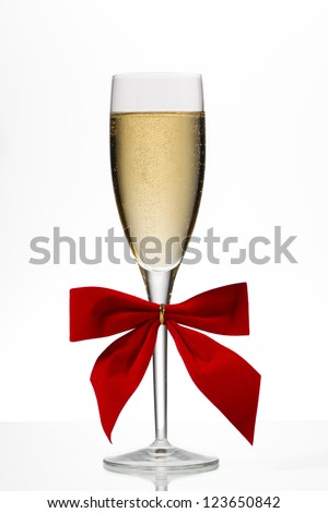 Champagne flute with red ribbon on white background - stock photo