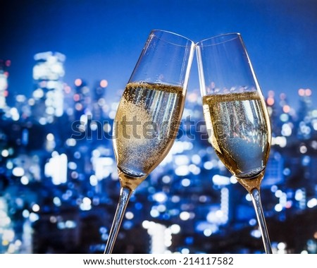 champagne flutes with golden bubbles make cheers on blue city night lights background with space for text - stock photo