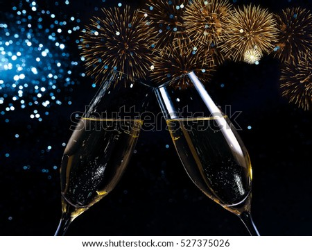 champagne flutes with golden bubbles make cheers on blue light bokeh and fireworks sparkle background, happy new year concept