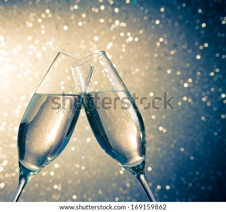 champagne flutes with golden bubbles make cheers on blue light bokeh background with space for text - stock photo