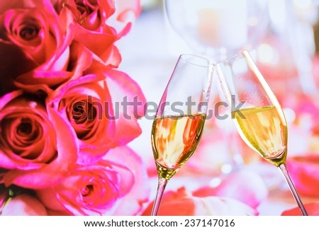 champagne flutes with golden bubbles make cheers on wedding roses flowers background - stock photo