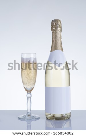 Champagne glass and a bottle with natural reflection, studio shot on grey background  - stock photo