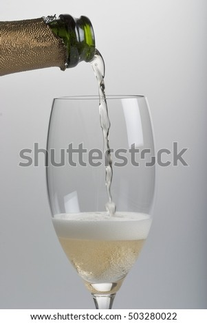Champagne glass filling with bottle