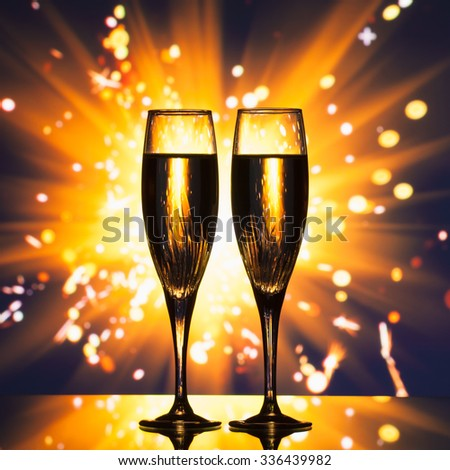 champagne glass silhouette against sparkler background