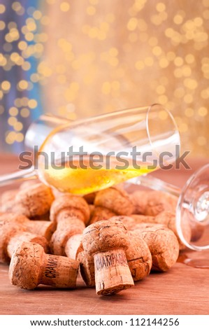 Champagne glass spill over a stack of corks - stock photo