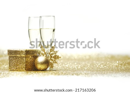 Champagne glasses and christmas decor on glitters with white copy space - stock photo
