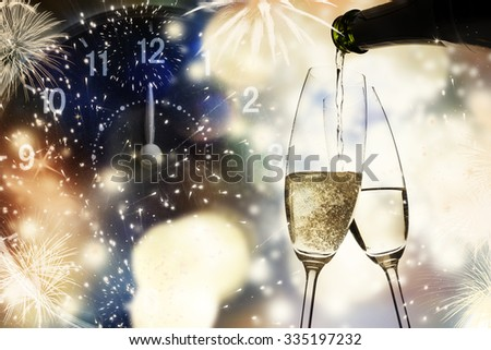 Champagne glasses, clock and fireworks at midnight - stock photo