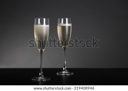 Champagne glasses for New Year and holidays, studio shot on gray background  - stock photo