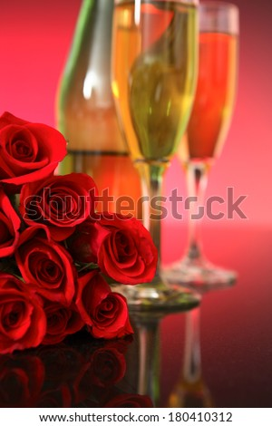 Champagne glasses with bottle and a dozen red roses on pink background  - stock photo