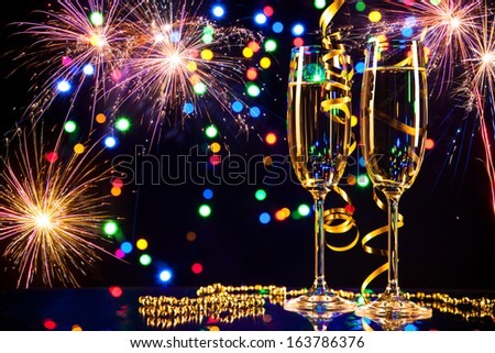 Champagne glasses with fireworks on background - stock photo