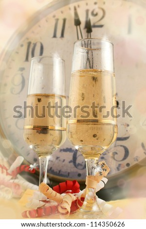 Champagne in glasses with ribbons with new years countdown vintage clock in the background - stock photo