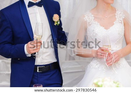 Champagne in hands of the bride and groom - stock photo