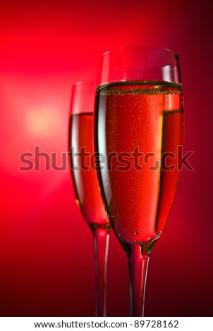 champagne in wineglass on a red background. - stock photo