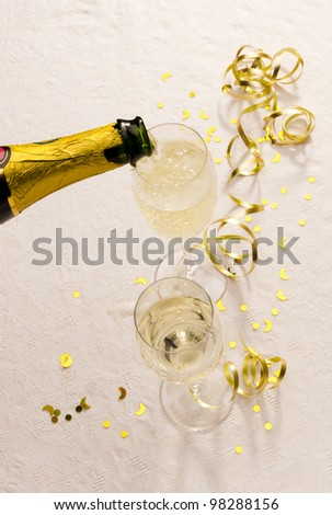 Champagne is poured from a bottle into two glasses beside golden table decorations - stock photo