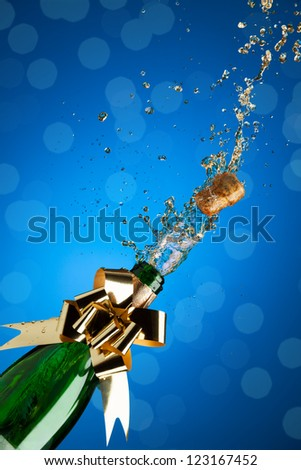 Champagne splashes from bottle and popping cork on blue background - stock photo
