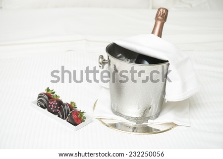 champagne, strawberries / which are dipped in choc-o-late / a lovely surprise - stock photo