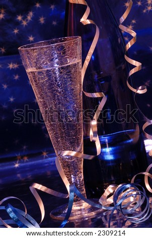 Champagne Toast - Crystal champagne flute and blue bottle of wine against a brilliant blue starry background.