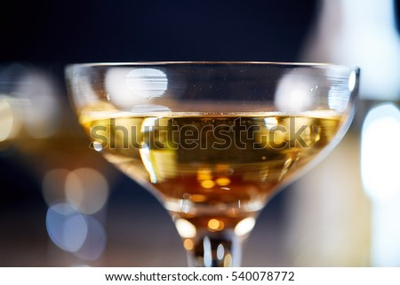 Champagne with bubbles in glass with background bokeh of glass and bottle