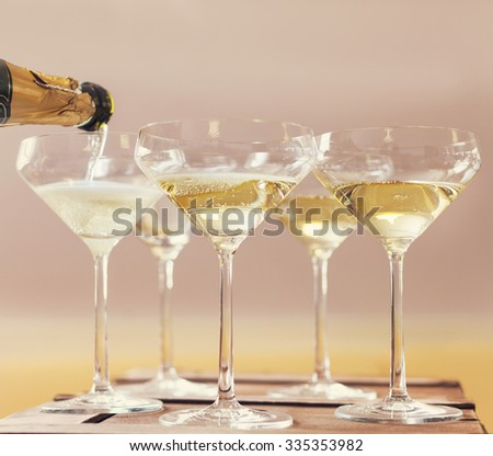Champaign being pored into glasses. Retro toned image - stock photo