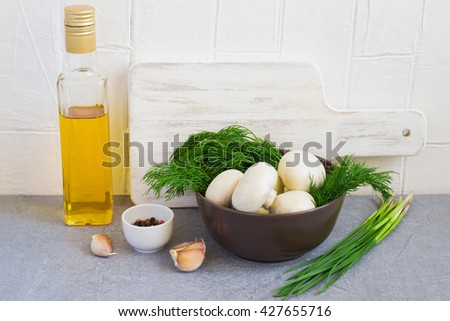 Champignon mushrooms and herbs in a bowl, cutting board, oil and spices - stock photo
