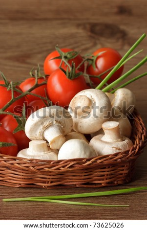 Champignons and cherry tomatoes in a basket on a wooden table. - stock photo