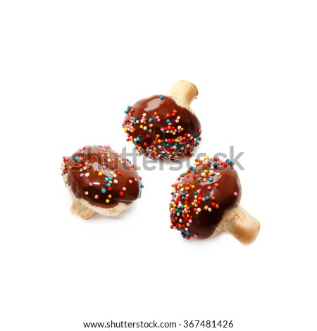champignons dipped in chocolate. mushrooms doused dark chocolate with multicolored sugar sprinkles. food porn concept. Isolated on white background - stock photo
