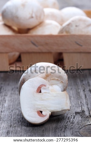 Champignons in a wooden box on old table - stock photo