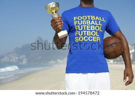 Champion Brazilian football player holding trophy and vintage soccer ball in international football t-shirt Ipanema Beach Rio de Janeiro Brazil - stock photo