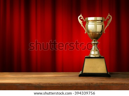 champion golden trophy on wood table with Red closed curtain background