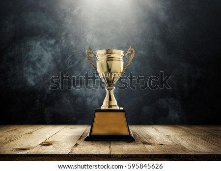 champion golden trophy placed on wooden table with dark background copy space ready for your design win concept.