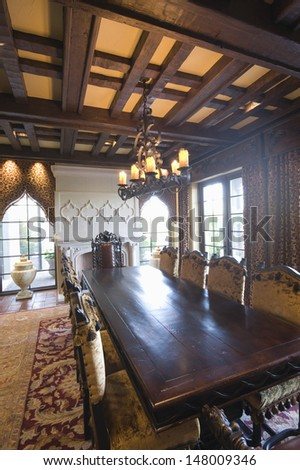 Chandelier hangs over dining table from wood beamed ceiling - stock photo