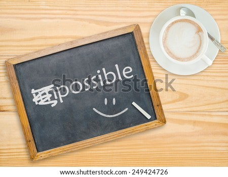 Change impossible to possible on chalkboard with coffee cup  - stock photo