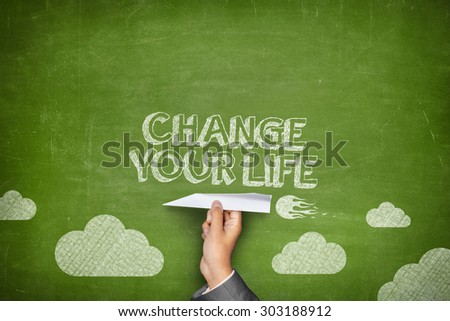 Change your life concept on green blackboard with businessman hand holding paper plane - stock photo