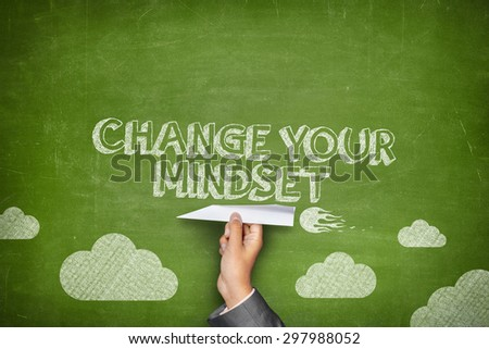 Change your mindset concept on green blackboard with businessman hand holding paper plane - stock photo