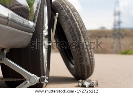 Changing a puncture with a close up view of the jack and the wheel spanner inserted over the wheel nuts with the spare tyre balanced alongside - stock photo