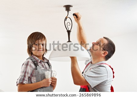 Changing an incandescent lightbulb with a fluorescent one - boy helping his father - stock photo