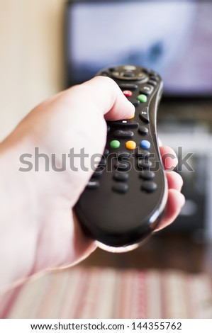 Changing channel with the tv remote control - stock photo