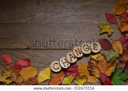changing colorful leaves on wooden planks and pieces of wood with the letters spelling CHANGE burnt in them - stock photo